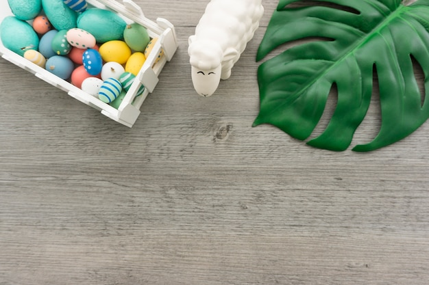 Wooden surface with green leaf, sheep and easter eggs