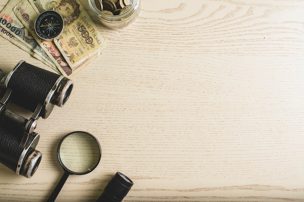Wooden surface with money and travel tools