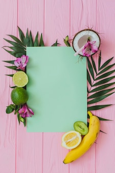 Wooden surface with piece of paper and fruits