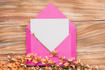 Wooden surface with pink envelope and blank paper