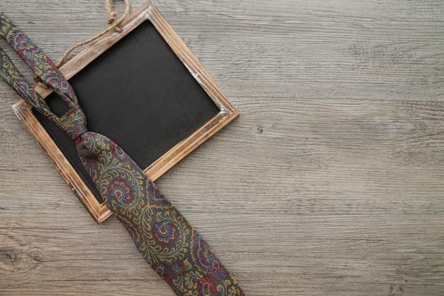 Superficie in legno con ardesia e cravatta per il giorno del padre