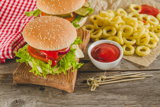 Wooden surface with tomato sauce, hamburgers and onion rings