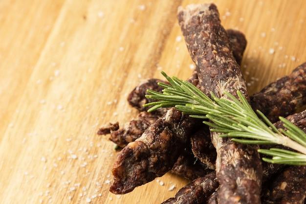 ローズマリーの調味料が付いている伝統的な南アフリカのdroworsが付いている木の表面