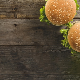 Wooden surface with two burgers and blank space