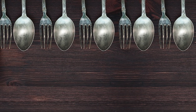 Wooden surface with vintage spoons and forks