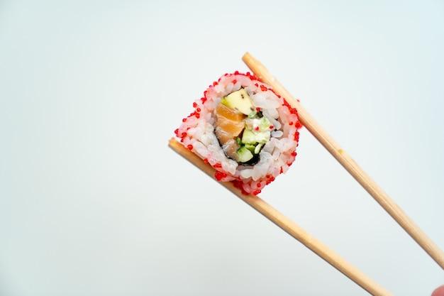 Деревянные палочки для суши держат ролл с красной икрой, рыбой, рисом и авокадо на белом фоне. заказ еды с доставкой онлайн. японская кухня.