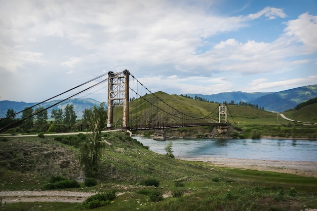 Деревянный подвесной мост через горную реку высоко в горах алтая.