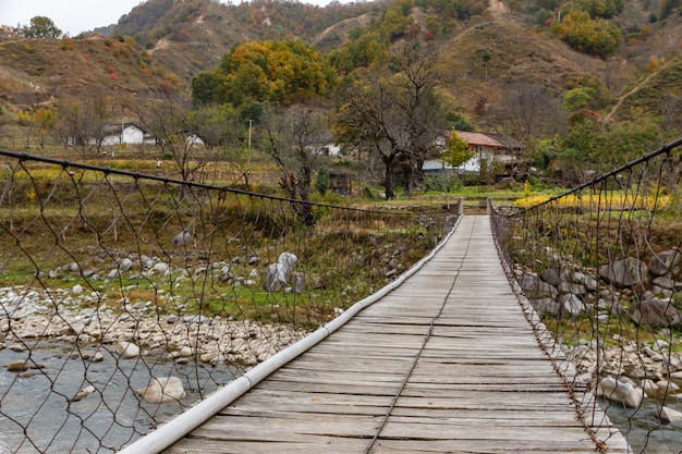 Wooden suspension bridge over a river in the mountains