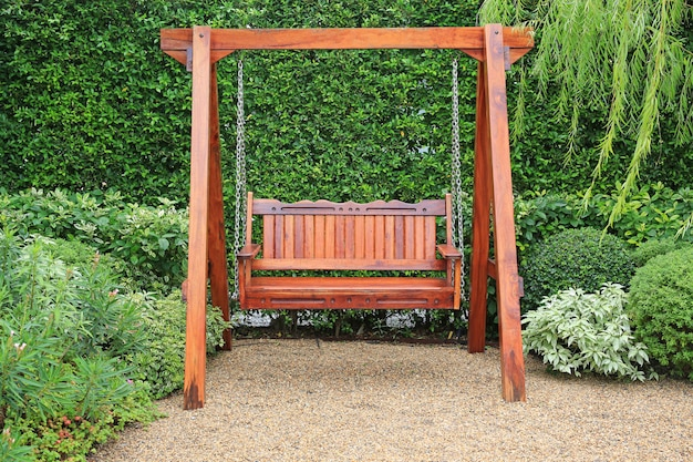 自然の緑豊かな庭園の木製スイングチェア