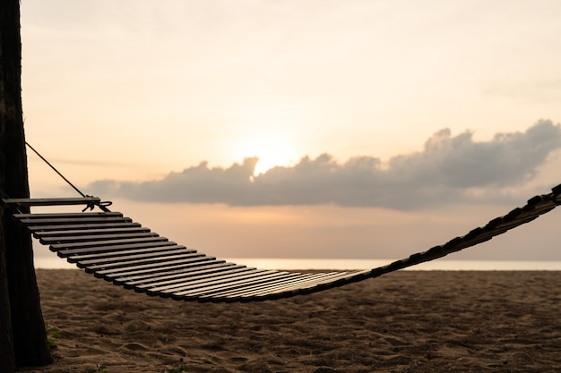 A wooden swing or cradle on the beach with beautiful cloud and sky.