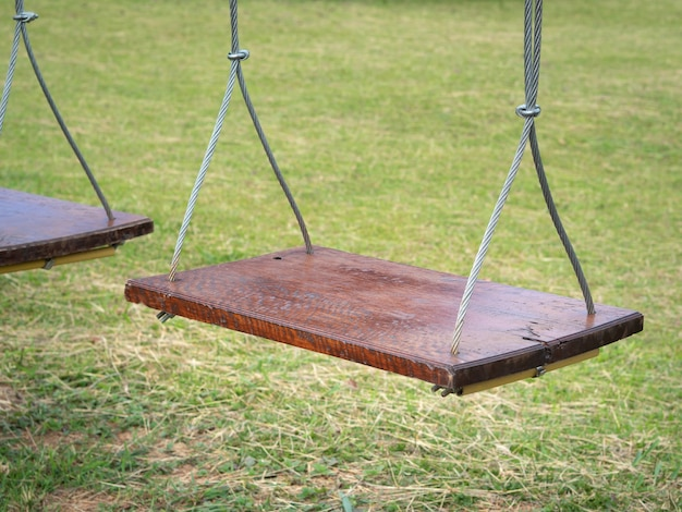 Wooden swing hanging in the garden or park.