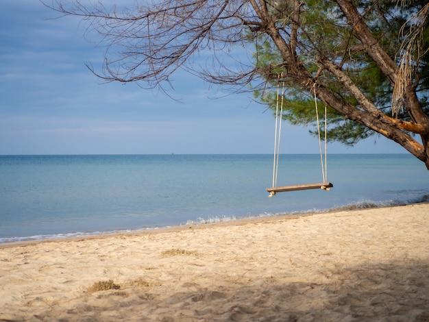 나무에 매달려 나무 그네 배경에 푸른 바다입니다.