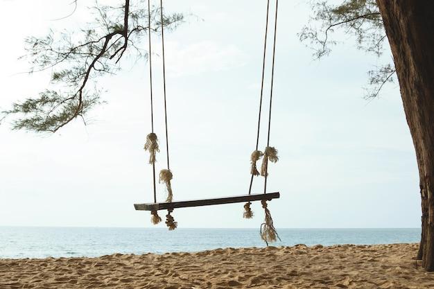 ビーチの木にぶら下がっている木製のブランコ