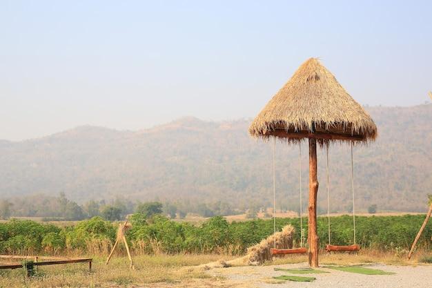 Wooden swing hanging under sunshade umbrella in the nature garden