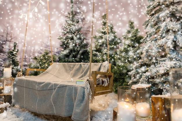 Деревянные качели с одеялом и книгой на нем в заснеженном парке или лесу с елями и пнями с большими свечами в стеклянных вазах, пока идет снег, концепция о празднике рождества и нового года