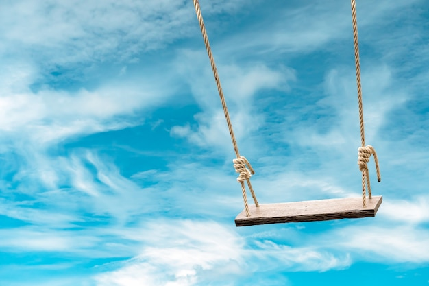 Wooden swing with pastel blue sky and cloud