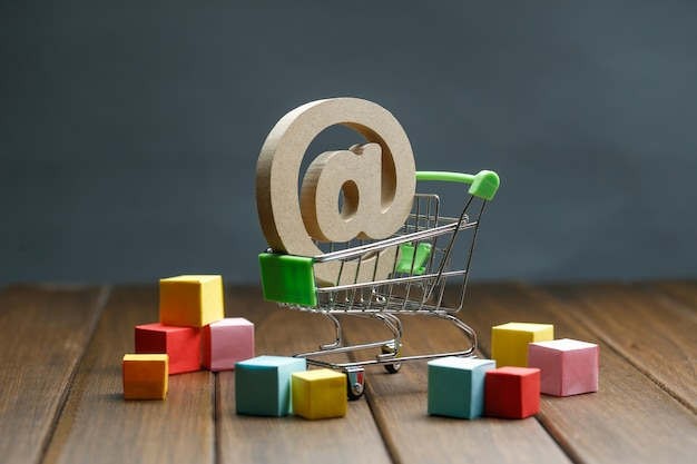 Wooden symbol @ in shopping cart, online shopping concept