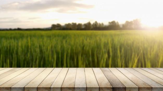 Деревянный стол против предпосылки поля риса расплывчатой.