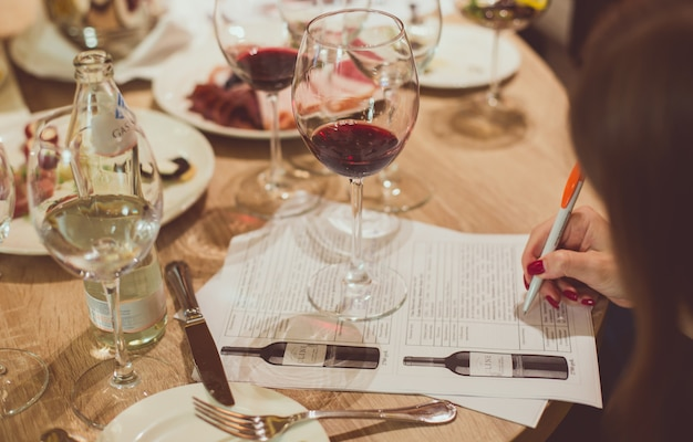 On a wooden table among glasses of wine and plates