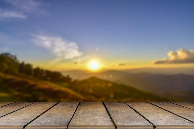나무 테이블과 아름다움의 흐림, 일몰 하늘, 그리고 배경으로 산.