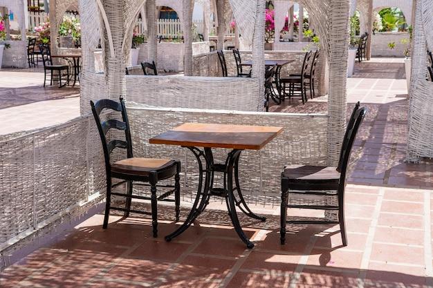 이집트 샤름 엘 셰이크(sharm el sheikh)의 홍해 옆 해변 카페에 있는 나무 테이블과 의자가 닫혀 있습니다.