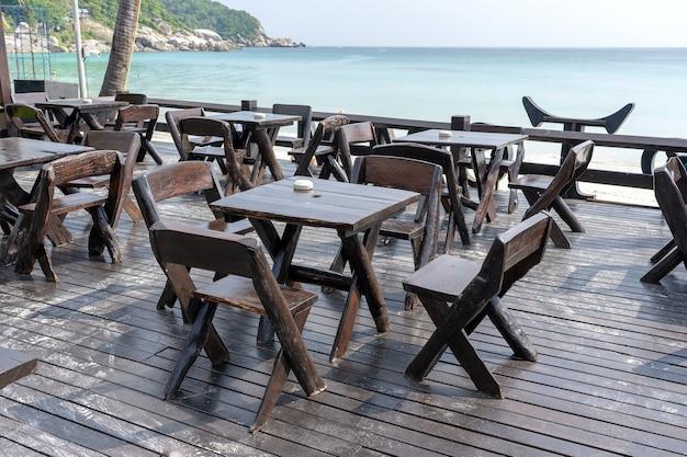 Деревянный стол и стулья в пустом пляжном кафе рядом с морской водой. закройте вверх. остров ко панган, таиланд