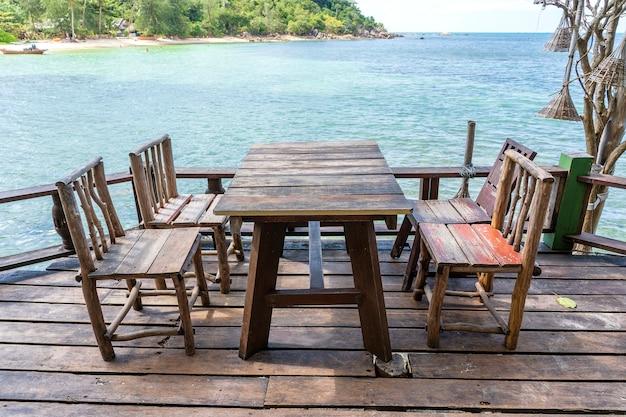 바닷물 옆에 있는 빈 해변 카페에 있는 나무 테이블과 의자. 확대. 태국 코팡안 섬