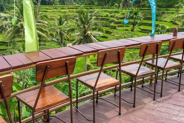 インドネシア、バリ島の棚田の隣にある空のトロピカルカフェの木製のテーブルと椅子をクローズアップ