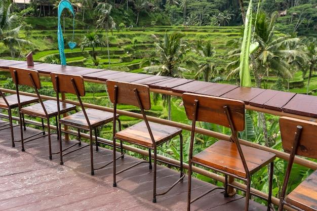 インドネシアのバリ島の棚田の隣にある空のトロピカルカフェの木製のテーブルと椅子をクローズアップ