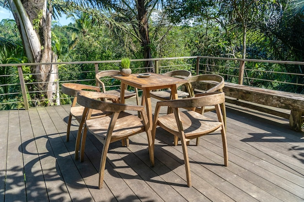 Деревянный стол и стулья в пустом тропическом кафе рядом с рисовыми террасами на острове бали, индонезия, крупным планом
