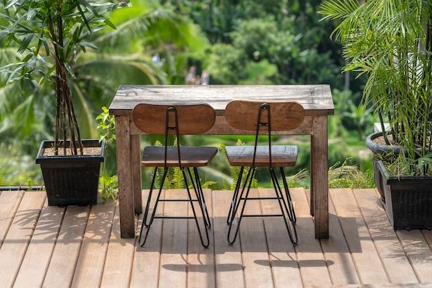 Деревянный стол и стулья в пустом тропическом кафе рядом с рисовыми террасами на острове бали, индонезия