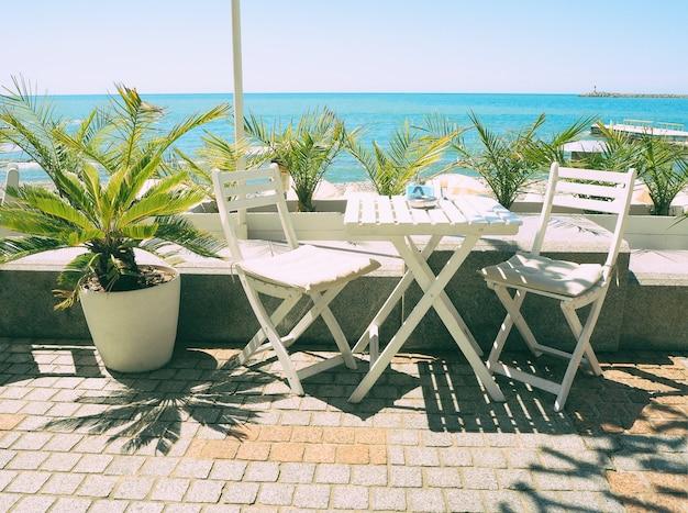 青い海とヤシの背景の屋外カフェの木製のテーブルと椅子