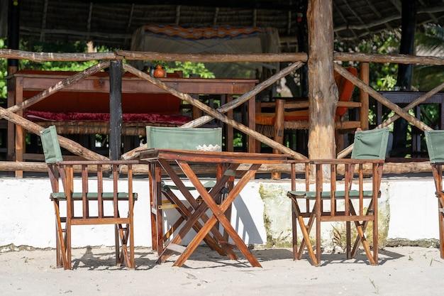 Деревянный стол и стулья у моря на тропическом песчаном пляже. открытый ресторан на пляже на острове занзибар, танзания, восточная африка