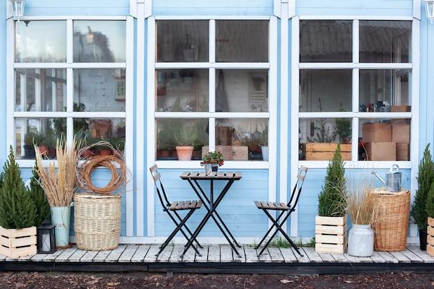 家のベランダに木製のテーブルと椅子。家具付きのエクステリアストリートカフェ。