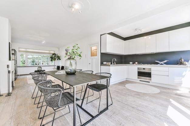Деревянный стол и удобные стулья возле кухонной мебели в современной светлой квартире