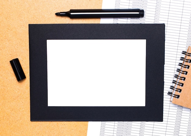 On a wooden table are a black open marker, a brown notepad and lst of paper in a black frame. top view with copy space.
