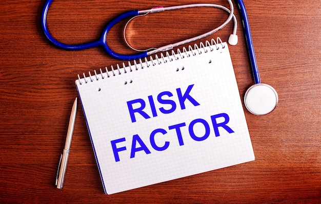 On a wooden table are a pen, a stethoscope, and a notebook labeled risk factor. medical concept.