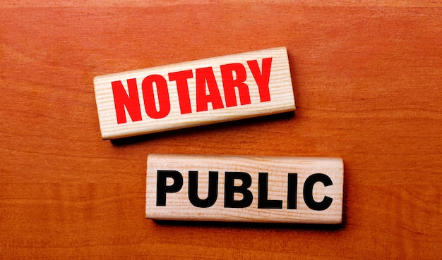 On a wooden table are two wooden blocks with the text notary public