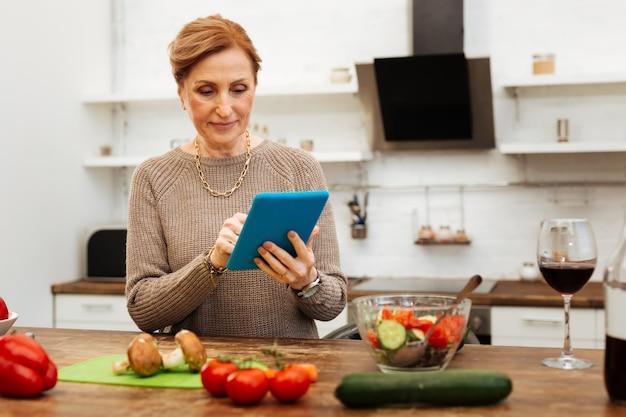 木製のテーブル。キッチンに滞在し、青いカバーでタブレットを運び、タイピングする気配りのある快適な女性