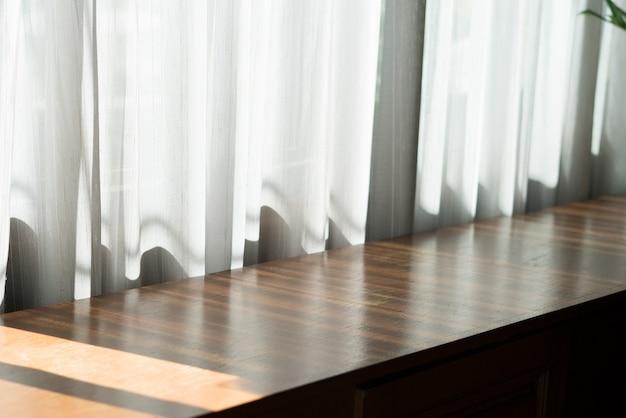 Предпосылка деревянного стола у окна в солнечный день.