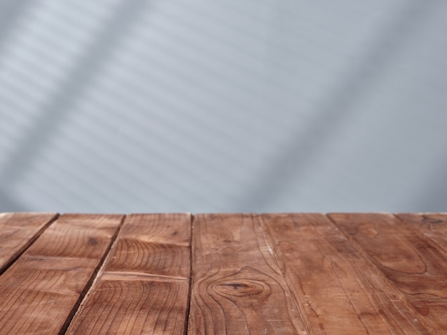 Wooden table on the background of a concrete wall with light from the window