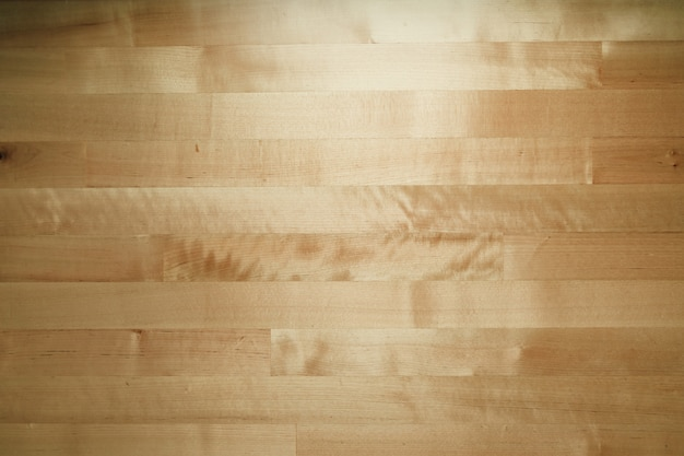 Wooden table background in low room light.