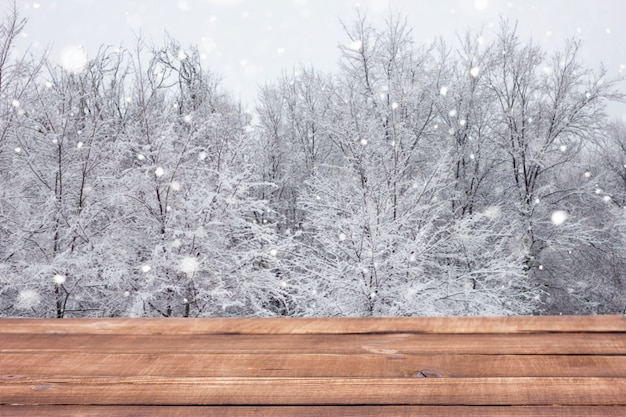 Wooden table on the background of the winter forest.