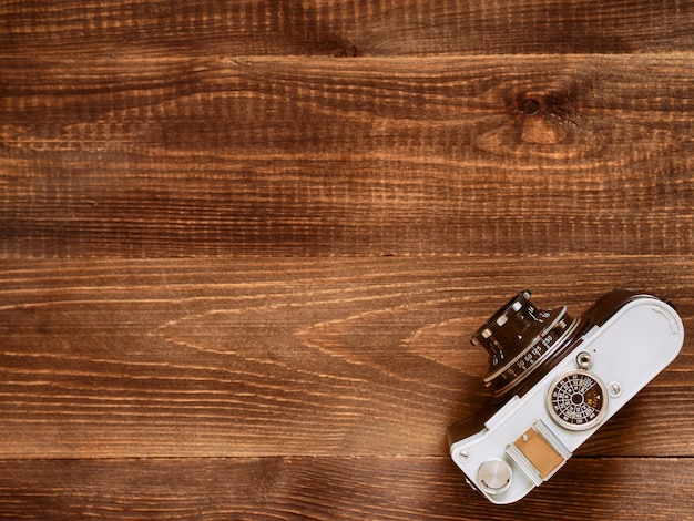 Wooden table background with old vintage camera. flat lay or top view