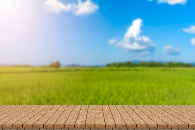 Wooden table and blur of beauty on sunny day on rice field with sky and mountains as background.
