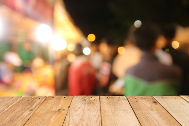 Wooden table board on front blurred night street background, copy space for presentation p