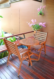 Wooden table and chairs on balcony at coffee shop.