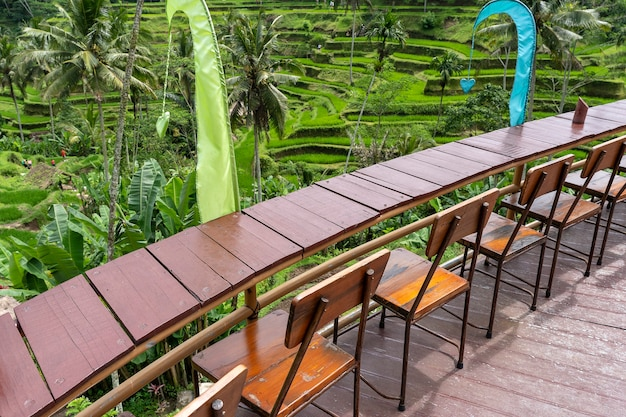 Wooden table and chairs in empty tropical cafe next to rice terraces in island bali, indonesia