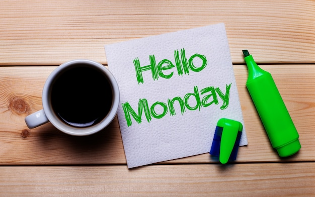 On a wooden table, a cup of coffee, a green marker and a napkin with the text hello monday