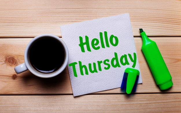 On a wooden table, a cup of coffee, a green marker and a napkin with the text hello thursday
